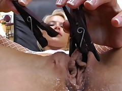 Shaved pussy is getting some pussy torture. The camera lens moves close up to film the clamps going down on it. The kinky whore really enjoys being molested.