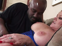 Horny aged lady Kate Faucett in black high heels gets her massive boobs licked and her pink cunt fingered by a black guy. Then well-endowed redhead sucks his big meat pole