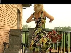 Golden-haired honey sunning nude on a balcony starts fitting on sexy darksome nylons